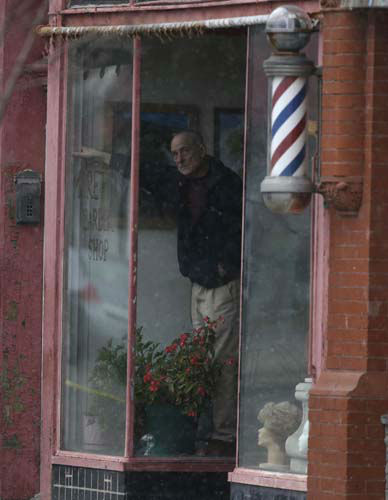 A man watches from the window of a barber shop as officials search down the street for a suspect in two shootings that killed four and injured at least two on, Wednesday, March 13, 2013 in Herkimer, N.Y. A man neighbors said rarely spoke to them started a fire in his apartment on Wednesday, shot four people dead at a couple of businesses in his hometown and a neighboring village and then exchanged gunfire with police officers who surrounded an abandoned building where he apparently was holed up, authorities said. &#40;AP Photo&#47;Mike Groll&#41; <span class=meta>(AP Photo&#47; Mike Groll)</span>