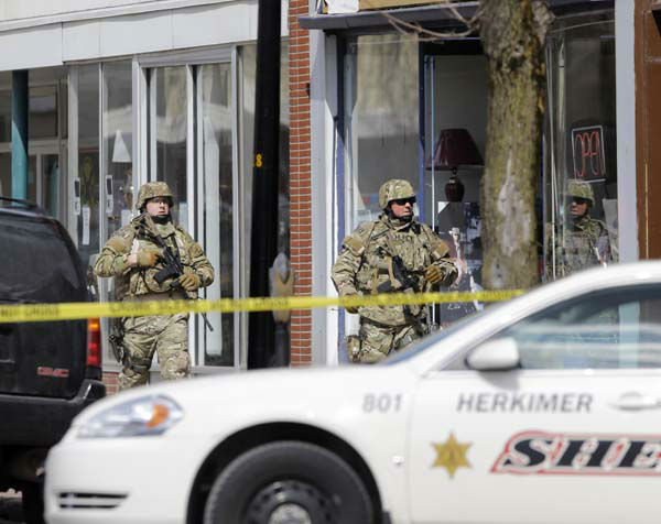 Law enforcement officers walk along Main Street in Herkimer, N.Y., while searching for a suspect in two shootings that killed four and injured at least two on, Wednesday, March 13, 2013. Authorities were looking for Kurt Meyers, said Joseph Malone, the police chief for Herkimer and Mohawk. Officials say guns and ammunition were found inside his Mohawk apartment after emergency crews were sent to a fire there Wednesday morning.  &#40;AP Photo&#47;Mike Groll&#41; <span class=meta>(AP Photo&#47; Mike Groll)</span>