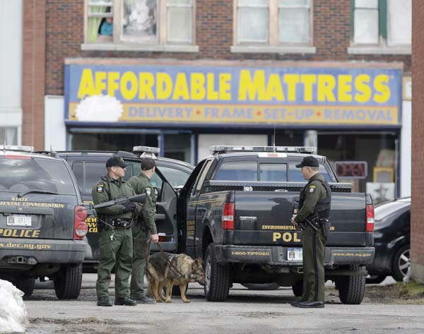 Law enforcement officers stand in an alley near Main Street while searching for a suspect in two shootings that killed four and injured at least two on Wednesday, March 13, 2013. Authorities were looking for Kurt Meyers, said Joseph Malone, the police chief for Herkimer and Mohawk. Officials say guns and ammunition were found inside his Mohawk apartment after emergency crews were sent to a fire there Wednesday morning.  &#40;AP Photo&#47;Mike Groll&#41; <span class=meta>(AP Photo&#47; Mike Groll)</span>