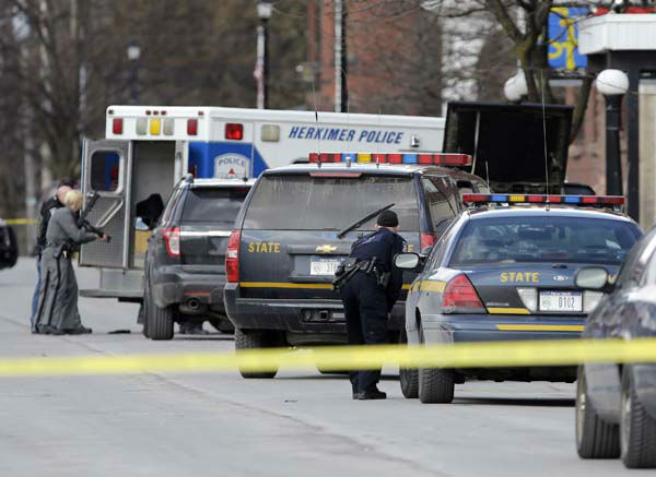 Law enforcement officers take cover along Main Street in Herkimer, N.Y., when shots were fired while they were searching for a suspect in two shootings that killed four and injured at least two on, Wednesday, March 13, 2013.  Authorities were looking for 64-year-old Kurt Meyers, said Herkimer Police Chief Joseph Malone. Officials say guns and ammunition were found inside his Mohawk apartment after emergency crews were sent to a fire there Wednesday morning.  &#40;AP Photo&#47;Mike Groll&#41; <span class=meta>(AP Photo&#47; Mike Groll)</span>
