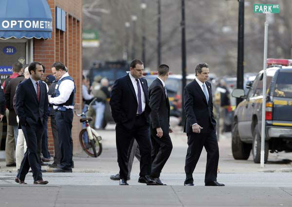 New York Gov. Andrew Cuomo, right, walks to a vehicle as law enforcement officers take cover along Main Street after shots were fired while they were searching for a suspect in two shootings that killed four and injured at least  two on, Wednesday, March 13, 2013, in Herkimer, N.Y. Authorities were looking for 64-year-old Kurt Meyers, said Herkimer Police Chief Joseph Malone. Officials say guns and ammunition were found inside his Mohawk apartment after emergency crews were sent to a fire there Wednesday morning.  &#40;AP Photo&#47;Mike Groll&#41; <span class=meta>(AP Photo&#47; Mike Groll)</span>
