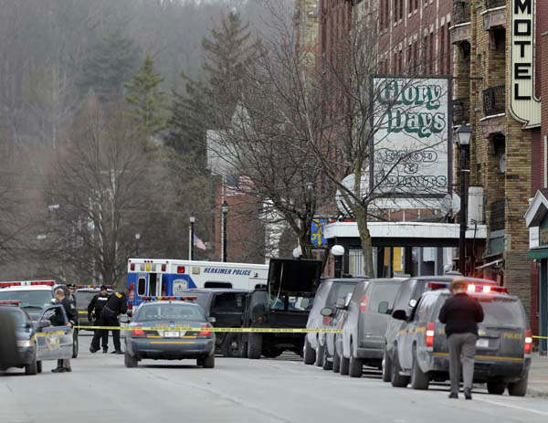 Law enforcement officials work outside the building where a man was killed after police stormed it following a standoff on, Thursday, March 14, 2013, in Herkimer, N.Y. The man was suspected of two shootings on Wednesday that killed four and injured two others. &#40;AP Photo&#47;Mike Groll&#41; <span class=meta>(AP Photo&#47; Mike Groll)</span>