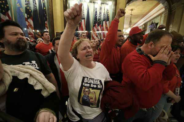 Protesters gather for a rally in the rotunda at the State Capitol in Lansing, Mich., Tuesday, Dec. 11, 2012. The crowd is protesting right-to-work legislation passed last week. Michigan could become the 24th state with a right-to-work law next week. Rules required a five-day wait before the House and Senate vote on each other&#39;s bills; lawmakers are scheduled to reconvene Tuesday and Gov. Snyder has pledged to sign the bills into law. &#40;AP Photo&#47;Paul Sancya&#41; <span class=meta>(AP Photo&#47; Paul Sancya)</span>