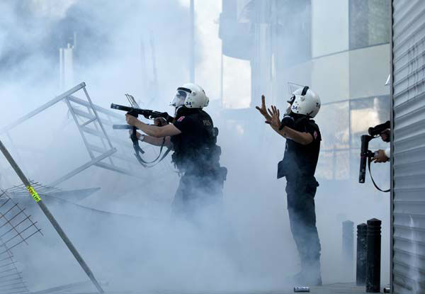 Turkish riot police fire tear gas during clashes at the Taksim Square in Istanbul Tuesday, June 11, 2013. Some hundreds of police in riot gear forced their way through barricades in the square early Tuesday, pushing many of the protesters who had occupied the square for more than a week into a nearby park. &#40;AP Photo&#47;Vadim Ghirda&#41; <span class=meta>(AP Photo&#47; Vadim Ghirda)</span>
