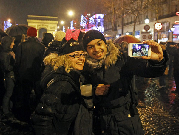 Revelers celebrate the New Year on the Champs Elysee in Paris, Tuesday Jan. 1, 2013.(AP Photo/Remy de la Mauviniere)