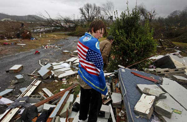 Will Carter, 15, wraps himself up in a towel he found while searching debris for the family dog, a pit bull named Niko, upon arriving to his damaged home from school following a tornado, Wednesday, Jan. 30, 2013, in Adairsville, Ga. A fierce storm system that roared across Georgia has left at least one person dead after it demolished buildings and flipped vehicles on Interstate 75 northwest of Atlanta. &#40;AP Photo&#47;David Goldman&#41; <span class=meta>(AP Photo&#47; David Goldman)</span>