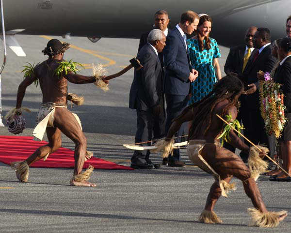 Britain&#39;s Prince William, fourth left, and his wife Kate, fifth left,  the Duke and Duchess of Cambridge, arrive at Honiara International Airport in Solomon Islands, Sunday, Sept. 16, 2012, as warriors in traditional dress dance around them.  &#40;AP Photo&#47;Rick Rycroft&#41; <span class=meta>(AP Photo&#47; Rick Rycroft)</span>