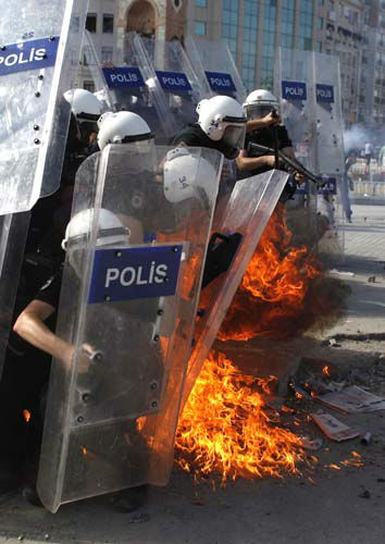 A petrol bomb explodes in front of  riot policemen during clashes in Taksim Square in Istanbul, Turkey, Tuesday, June 11, 2013. Hundreds of police in riot gear forced through barricades in Istanbul&#39;s central Taksim Square early Tuesday, pushing many of the protesters who had occupied the square for more than a week into a nearby park. &#40;AP Photo&#47;Kostas Tsironis&#41; <span class=meta>(AP Photo&#47; Kostas Tsironis)</span>