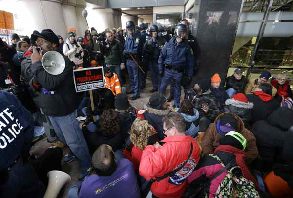 Protesters sit during a rally at the George W. Romney State Building, where Gov. Snyder has an office in Lansing, Mich., Tuesday, Dec. 11, 2012. The crowd is protesting right-to-work legislation passed last week. Michigan could become the 24th state with a right-to-work law next week. Rules required a five-day wait before the House and Senate vote on each other&#39;s bills; lawmakers are scheduled to reconvene Tuesday and Gov. Snyder has pledged to sign the bills into law. &#40;AP Photo&#47;Paul Sancya&#41; <span class=meta>(Photo&#47;Paul Sancya)</span>
