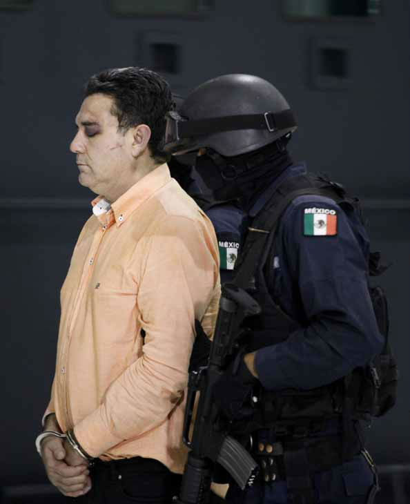 FILE - In this Nov. 8, 2010 file photo, police escort suspected drug trafficker Manuel Fernandez Valencia, alias &#34;The Pig,&#34; or &#34;La Puerca,&#34; as he is presented to the press at the federal police headquarters in Mexico City. According to federal police, Fernandez is an alleged member of the criminal organization led by Joaquin &#34;El Chapo&#34; Guzman and was arrested on Nov. 7, 2012 in the northern city of Culiacan in Mexico&#39;s Sinaloa state. Fernandez&#39;s nickname came from his &#34;piggish&#34; style of killing rivals. He was also known as &#34;The Animal.&#34; &#40;AP Photo&#47;Eduardo Verdugo, File&#41; <span class=meta>(AP Photo&#47; Eduardo Verdugo)</span>