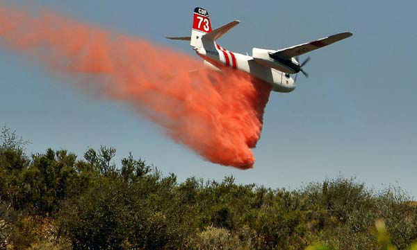 A firefighting aircraft drops fire retardant along a hill side near Thousand Oaks, Calif. on Thursday, May 2, 2013. A 2,000-acre blaze that began in the Camarillo area along U.S. 101 in Ventura County was uncontained. It prompted the evacuation of a Thousand Oaks neighborhood and the campus of California State University, Channel Islands. At least a half-dozen RVs burned in a parking area enclosed by brushy hills. Embers scattered along ridges and into neighborhoods abutting the brush lands and smoke streamed for miles. More than 200 firefighters were aided by water- and fire retardant-dropping aircraft. &#40;AP Photo&#47;Nick Ut&#41; <span class=meta>(AP Photo&#47; Nick Ut)</span>