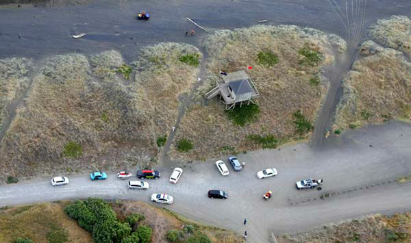 In this aerial photo, emergency vehicles are parked at Muriwai Beach near Auckland, New Zealand, Wednesday, Feb. 27, 2013, following a fatal shark attack. Police said a man was found dead in the water Wednesday afternoon after being &#34;bitten by a large shark.&#34; Police and surf lifesavers recovered the man&#39;s body. The police statement said Muriwai Beach near the city of Auckland has been closed. &#40;AP Photo&#47;New Zealand Herald, Chris Gorman&#41; NEW ZEALAND OUT, AUSTRALIA OUT <span class=meta>(AP Photo&#47; Chris Gorman)</span>