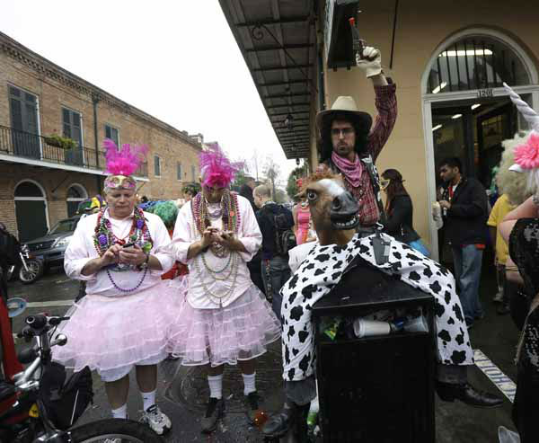 "<div class=""meta image-caption""><div class=""origin-logo origin-image ""><span></span></div><span class=""caption-text"">A man dressed as a cowboy holding a horse head,  sits on a trash can next to two men in pink dresses sending text messages during Mardi Gras in the French Quarter of New Orleans, Tuesday, Feb. 12, 2013.  Despite threatening skies, the Mardi Gras party carried on as thousands of costumed revelers cheered glitzy floats with make-believe monarchs in an all-out bash before Lent.   Crowds were a little smaller than recent years, perhaps influenced by the forecast of rain. Still, parades went off as scheduled even as a fog settled over the riverfront and downtown areas. (AP Photo/Gerald Herbert)</span></div>"