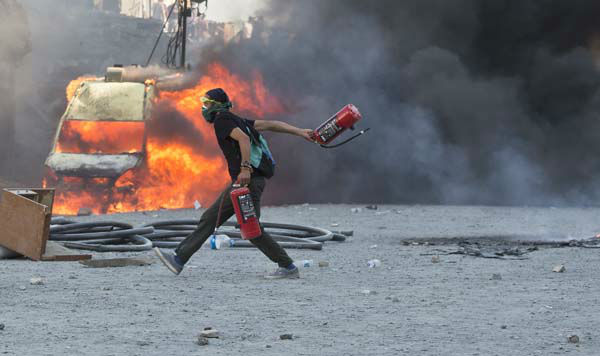 A man runs carrying fire extinguishers past a burning van during clashes at the Taksim Square in Istanbul Tuesday, June 11, 2013. Hundreds of police in riot gear forced through barricades in the square early Tuesday, pushing many of the protesters who had occupied the square for more than a week into a nearby park. &#40;AP Photo&#47;Vadim Ghirda&#41; <span class=meta>(AP Photo&#47; Vadim Ghirda)</span>