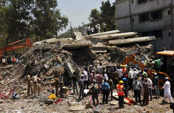 People gather around a heap of debris at the site of a building collapsed as a rescue operation continues on the outskirts of Mumbai, India, Friday, April 5, 2013. A half-finished building that was being constructed illegally in a suburb of India&#39;s financial capital collapsed, killing 35 people and injuring more than 50 others, police said Friday. &#40;AP Photo&#47;Rajanish Kakade&#41; <span class=meta>(AP Photo&#47; Rajanish Kakade)</span>