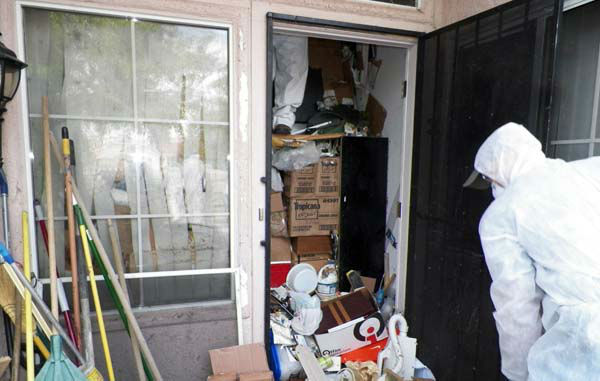 This photo provided by the City of Las Vegas via the Las Vegas Review-Journal shows a worker during a cleanup of the interior of hoarder Kenneth Epstein&#39;s home in Las Vegas. Officials began hauling away items from Kenneth Epstein&#39;s home on Friday, Oct. 5, 2012 after they found materials stacked from floor to ceiling inside and declared it uninhabitable, the Las Vegas Review-Journal reported. In all, a private removal company was working with officials to remove about 15 truckloads of materials. &#40;AP Photo&#47;City of Las Vegas via Las Vegas Review-Journal&#41; <span class=meta>(AP Photo&#47; Uncredited)</span>