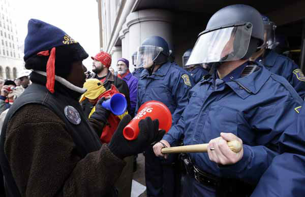 "<div class=""meta image-caption""><div class=""origin-logo origin-image ""><span></span></div><span class=""caption-text"">A protester rallies in front of Michigan State Police at the George W. Romney State Building, where Gov. Snyder has an office in Lansing, Mich., Tuesday, Dec. 11, 2012. The crowd is protesting right-to-work legislation passed last week. Michigan could become the 24th state with a right-to-work law next week. Rules required a five-day wait before the House and Senate vote on each other's bills; lawmakers are scheduled to reconvene Tuesday and Gov. Snyder has pledged to sign the bills into law. (AP Photo/Paul Sancya) (AP Photo/ Paul Sancya)</span></div>"
