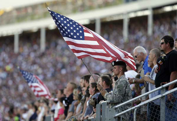 A soldier holds a United States flag during the national anthem before the NASCAR Sprint Cup series Coca-Cola 600 auto race at Charlotte Motor Speedway in Concord, N.C., Sunday, May 26, 2013. &#40;AP Photo&#47;Chuck Burton&#41; <span class=meta>(AP Photo&#47; Chuck Burton)</span>