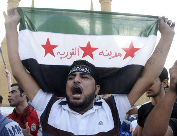 A supporter of Sunni hard line preacher Sheikh Ahmad Assir holds up a Syrian revolution flag with Arabic that reads : &#34;the Syrian town of Qourieh,&#34; as he chants slogans during a protest  against an anti-Islam movie, in Beirut, Lebanon, Friday, Sept. 21, 2012. Anger over insults to Islam&#39;s Prophet Muhammad isn&#39;t enough to bring Lebanon&#39;s divided Sunni and Shiite Muslims together. The two sects, which have been locked in sometimes violent political competition, held separate protests Friday and even threw gibes as Sunni protesters accused Shiite Hezbollah of using the demonstrators to distract from the fighting in neighboring Syria. &#40;AP Photo&#47;Ahmad Omar&#41; <span class=meta>(AP Photo&#47; Ahmad Omar)</span>