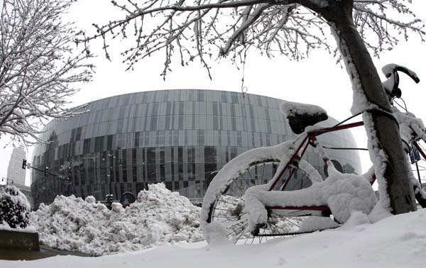 Snow covers trees and a bike outside the Sprint Center, Sunday, March 24, 2013, in Kansas City, Mo. The city was preparing for the third round of the NCAA college basketball tournament at the arena after the region received 6-10 inches of snow overnight. &#40;AP Photo&#47;Charlie Riedel&#41; <span class=meta>(AP Photo&#47; Charlie Riedel)</span>