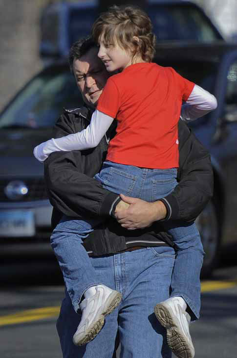 A man carries a child away from the area of a shooting at the Sandy Hook Elementary School in Newtown, Conn., about 60 miles &#40;96 kilometers&#41; northeast of New York City, Friday, Dec. 14, 2012.  A man opened fire Friday inside two classrooms at the school where his mother worked as a teacher, killing 26 people, including 20 children.  The killer, armed with two handguns, committed suicide at the school and another person was found dead at a second scene, bringing the toll to 28, authorities said. A law enforcement official identified the gunman as 20-year-old Adam Lanza.  &#40;AP Photo&#47;Jessica Hill&#41; <span class=meta>(AP Photo&#47; Jessica Hill)</span>