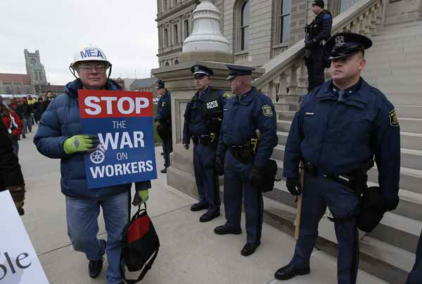 A protester walks past Michigan State Police at the State Capitol in Lansing, Mich., Tuesday, Dec. 11, 2012. The crowd is protesting right-to-work legislation passed last week. Michigan could become the 24th state with a right-to-work law next week. Rules required a five-day wait before the House and Senate vote on each other&#39;s bills; lawmakers are scheduled to reconvene Tuesday and Gov. Snyder has pledged to sign the bills into law. &#40;AP Photo&#47;Paul Sancya&#41; <span class=meta>(AP Photo&#47; Paul Sancya)</span>