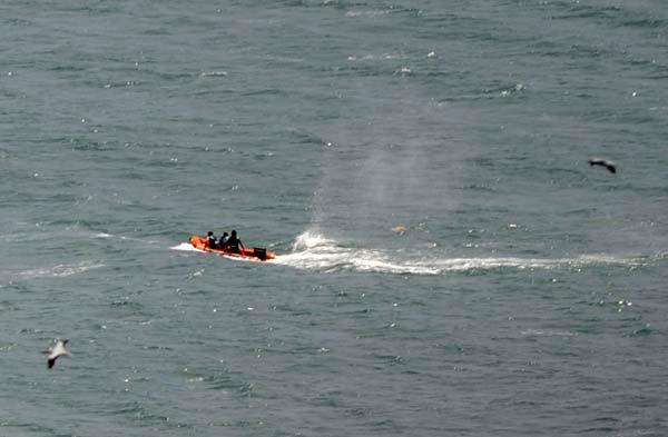 Police in inflatable rubber boats shoot at a shark off Muriwai Beach near Auckland, New Zealand, Wednesday, Feb. 27, 2013, as they attempt to retrieve a body following a fatal shark attack. Police said a man was found dead in the water after being &#34;bitten by a large shark.&#34; &#40;AP Photo&#47;Ross Land&#41; NEW ZEALAND OUT, NO SALES <span class=meta>(AP Photo&#47; Ross Land)</span>