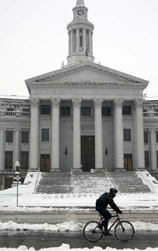 A lone bicyclist rides past the Denver City&#47;County Building in Denver as a spring storm packing high winds and heavy snow sweeps over Colorado&#39;s Front Range and on to the eastern plains on Saturday, March 23, 2013. Forecasters predict up to a foot of snow will fall in some locations in Colorado before the storm heads toward the nation&#39;s midsection. &#40;AP Photo&#47;David Zalubowski&#41; <span class=meta>(AP Photo&#47; David Zalubowski)</span>