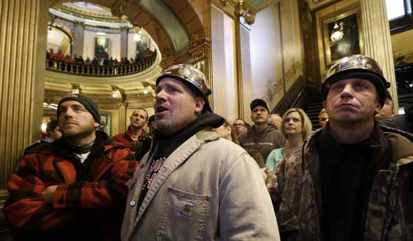 Union members Brian Brissette, of Auburn, Mich., from left, Tom Gazley, of Romeo, Mich., and Eric Kozlow, of Warren, Mich., watch the Michigan House of Representatives vote on a television in the at the State Capitol in Lansing, Mich., Tuesday, Dec. 11, 2012. The crowd is protesting right-to-work legislation passed last week. Michigan could become the 24th state with a right-to-work law next week. Rules required a five-day wait before the House and Senate vote on each other&#39;s bills; lawmakers are scheduled to reconvene Tuesday and Gov. Snyder has pledged to sign the bills into law. &#40;AP Photo&#47;Paul Sancya&#41; <span class=meta>(AP Photo&#47; Paul Sancya)</span>