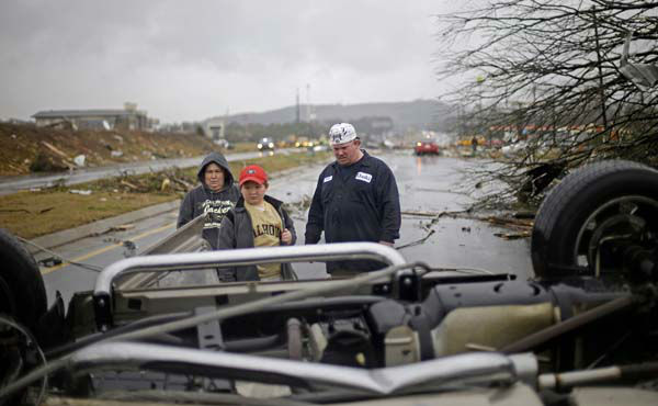 Tommy Stouffer, right, looks at his overturned car with his son Jonathan, 11, center, and wife, Norma Croft, left, after a tornado picked it up from the parking lot where he was working across the street and dumped it in the middle of the road, Wednesday, Jan. 30, 2013, in Adairsville, Ga. A fierce storm system that roared across Georgia has left at least one person dead after it demolished buildings and flipped vehicles on Interstate 75 northwest of Atlanta. &#40;AP Photo&#47;David Goldman&#41; <span class=meta>(AP Photo&#47; David Goldman)</span>