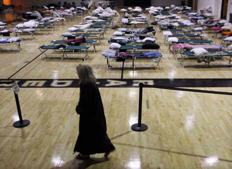 "<div class=""meta ""><span class=""caption-text "">A person walks through a makeshift shelter in a gymnasium at Toms River East High School as they arrive to vote Tuesday, Nov. 6, 2012, in Toms River, N.J.  N.J. Voter turnout was heavy in several storm-ravaged Jersey Shore towns, with many voters expressing relief and even elation at being able to vote at all, considering the devastation.  (AP Photo/Mel Evans) (AP Photo/ Mel Evans)</span></div>"