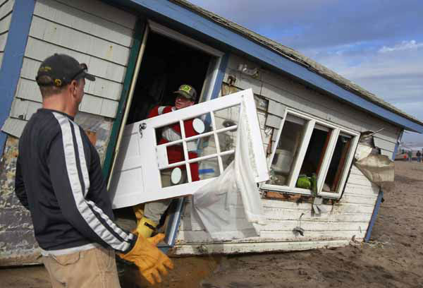 Christopher Hannafin, center, and Pete Duhamel, left, both of South Kingstown, R.I., salvage items, including a door, from a friend&#39;s cottage destroyed by Superstorm Sandy, on Roy Carpenter&#39;s Beach, in the village of Matunuck, in South Kingstown, Tuesday, Oct. 30, 2012. Sandy, the storm that made landfall Monday, caused multiple fatalities, halted mass transit and cut power to more than 6 million homes and businesses. &#40;AP Photo&#47;Steven Senne&#41; <span class=meta>(AP Photo&#47; Steven Senne)</span>