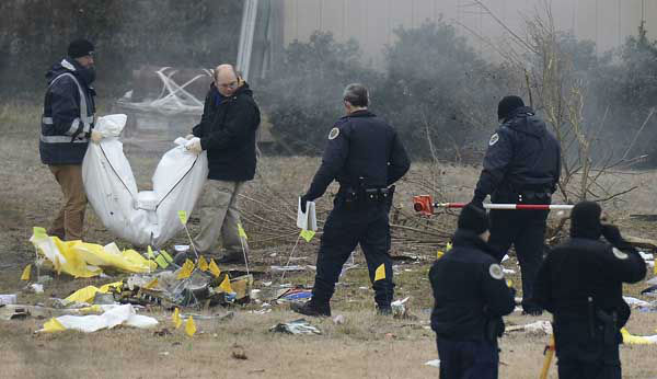 Investigators carry a body out from the crash site on Tuesday, Feb. 4, 2014 near Nashville.  The small plane crashed on Monday,  near a YMCA in suburban Nashville, killing everyone on board and damaging cars in the parking lot. Authorities believe four members of the same family were on board the flight, which crashed near in Bellevue.   The Gulfstream 690C departed from Great Bend Municipal Airport in Great Bend, Kansas, Monday afternoon around 2:45 p.m.,  and crashed 16 kilometres south of John C. Tune Airport in Nashville about 5 p.m.  &#40;AP Photo&#47;Mark Zaleski&#41; <span class=meta>(Photo&#47;Mark Zaleski)</span>