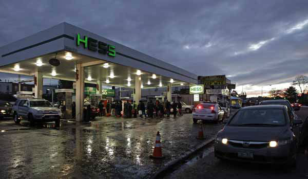 People with plastic containers and cars wait on line for gasoline at a Hess station in the Brooklyn borough of New York where gas is still scarce, Thursday, Nov. 8, 2012. Fuel shortages and distribution delays that led to gas hoarding have prompted New York City and Long Island to initiate an even-odd gas rationing plan which begins Friday at 6 a.m. in New York and 5 a.m. in Long Island. &#40;AP Photo&#47;Kathy Willens&#41; <span class=meta>(AP Photo&#47; Kathy Willens)</span>