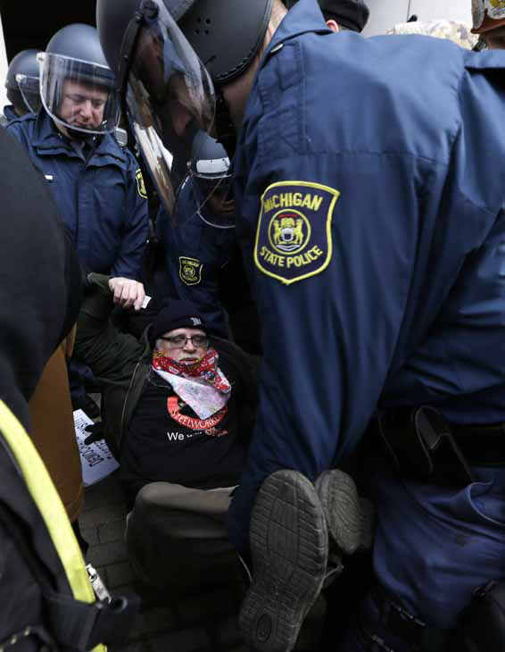 Michigan State Police carry a protester from a rally at the George W. Romney State Building, where Gov. Snyder has an office in Lansing, Mich., Tuesday, Dec. 11, 2012. The crowd is protesting right-to-work legislation passed last week. Michigan could become the 24th state with a right-to-work law next week. Rules required a five-day wait before the House and Senate vote on each other&#39;s bills; lawmakers are scheduled to reconvene Tuesday and Gov. Snyder has pledged to sign the bills into law. &#40;AP Photo&#47;Paul Sancya&#41; <span class=meta>(AP Photo&#47; Paul Sancya)</span>