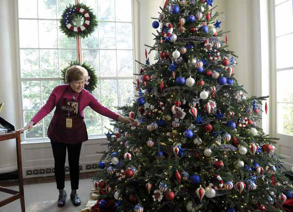Volunteer Paulette Marini describes the decorations on the tree in the East Landing of White House in Washington, Wednesday, Nov. 28, 2012, during a preview of the holiday deocrations. The decorations pay tribute to the Armed Forces and their families. The theme for the White House Christmas 2012 is Joy to All. &#40;AP Photo&#47;Susan Walsh&#41; <span class=meta>(AP Photo&#47; Susan Walsh)</span>
