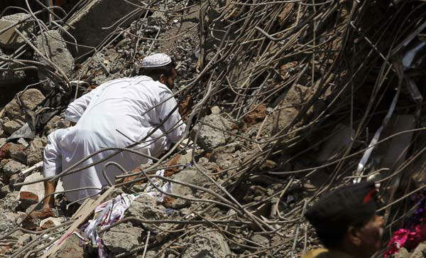 An Indian man looks for survivors in the debris of a building that collapsed on the outskirts of Mumbai, India, Friday, April 5, 2013. The half-finished building that was being constructed illegally in a suburb of India&#39;s financial capital collapsed on Thursday, killing 35 people and injuring more than 50 others, police said Friday. &#40;AP Photo&#47;Rajanish Kakade&#41; <span class=meta>(AP Photo&#47; Rajanish Kakade)</span>