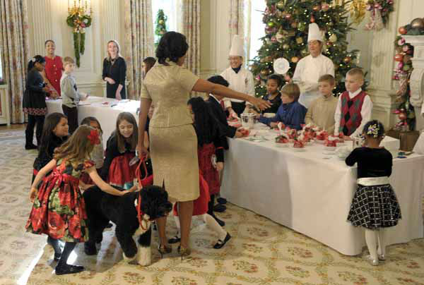 School children pet Obama family dog Bo, as First lady Michelle Obama looks at the holiday crafts the children were creating during a visit to the State Dining Room in the White House in Washington, Wednesday, Nov. 28, 2012. The crafts were part of the preview of the holiday decorations at the White House. The theme for the White House Christmas 2012 is Joy to All. School children were also in the State Dining Room decorating holiday treats. &#40;AP Photo&#47;Susan Walsh&#41; <span class=meta>(AP Photo&#47; Susan Walsh)</span>