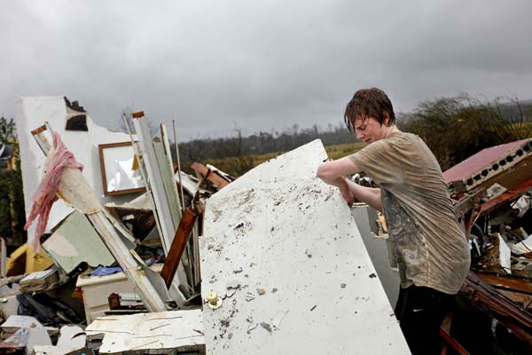 Will Carter, 15, pulls up debris while searching for the family dog, a pit bull named Niko, upon arriving to his damaged home from school following a tornado, Wednesday, Jan. 30, 2013, in Adairsville, Ga. A fierce storm system that roared across Georgia has left at least one person dead after it demolished buildings and flipped vehicles on Interstate 75 northwest of Atlanta. &#40;AP Photo&#47;David Goldman&#41; <span class=meta>(AP Photo&#47; David Goldman)</span>