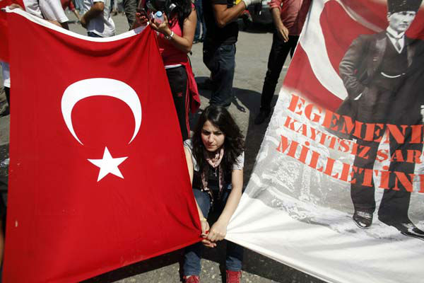 "<div class=""meta ""><span class=""caption-text "">A protester holding a Turkish flag and a flag decorated with the image of Turkeys' founder Mustafa Kemal Ataturk sits after clashes in Taksim square in Istanbul, Tuesday, June 11, 2013. Hundreds of police in riot gear forced through barricades in Istanbul's central Taksim Square early Tuesday, pushing many of the protesters who had occupied the square for more than a week into a nearby park. The slogan on the banner reads ""Sovereignty unconditionally belongs to the nation"" . (AP Photo/Kostas Tsironis) (AP Photo/ Kostas Tsironis)</span></div>"