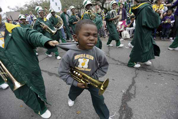 Cardale Waterhouse gets a helping hand from an older band member as he marches with the Medard Nelson Charter School band during the Krewe of Mid-City Mardi Gras parade in New Orleans, Sunday, Feb. 10, 2013. &#40;AP Photo&#47;Gerald Herbert&#41; <span class=meta>(AP Photo&#47; Gerald Herbert)</span>