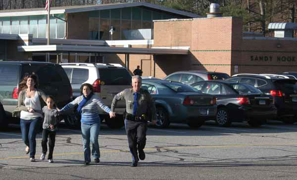 In this photo provided by the Newtown Bee, a police officer leads two women and a child from Sandy Hook Elementary School in Newtown, Conn., where a gunman opened fire, killing 26 people, including 20 children, Friday, Dec. 14, 2012. &#40;AP Photo&#47;Newtown Bee, Shannon Hicks&#41; MANDATORY CREDIT: NEWTOWN BEE, SHANNON HICKS <span class=meta>(AP Photo&#47; Shannon Hicks)</span>