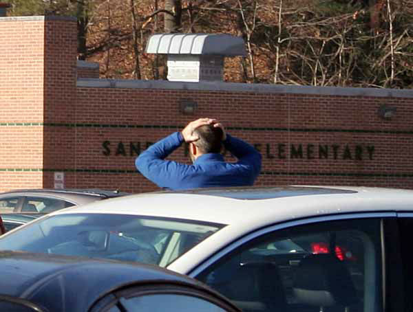 In this photo provided by the Newtown Bee, a man stands with his hands on his head outside of Sandy Hook Elementary School in Newtown, Conn., where authorities say a gunman opened fire, killing 26 people, including 20 children, Friday, Dec. 14, 2012. &#40;AP Photo&#47;Newtown Bee, Shannon Hicks&#41; MANDATORY CREDIT: NEWTOWN BEE, SHANNON HICKS <span class=meta>(AP Photo&#47; Shannon Hicks)</span>