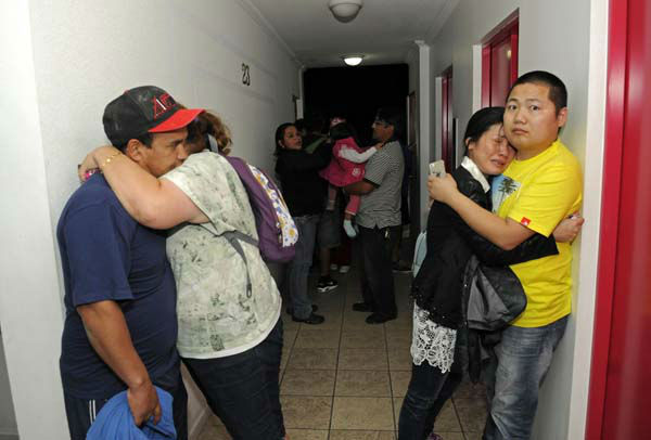 People embrace on the upper floor of an apartment building located a few blocks from the coast where they gathered to avoid a possible tsunami after an earthquake in Iquique, Chile, Tuesday, April 1, 2014. A powerful magnitude-8.2 earthquake struck off Chile&#39;s northern coast Tuesday night. There were no immediate reports of injuries or major damage, but buildings shook in nearby Peru and in Bolivia&#39;s high altitude capital of La Paz. &#40;AP Photo&#47;Cristian Viveros&#41;  <span class=meta>(Photo&#47;Cristian Viveros)</span>