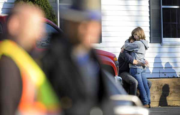 People embrace at a firehouse staging area for family around near the scene of a shooting at the Sandy Hook Elementary School in Newtown, Conn., about 60 miles &#40;96 kilometers&#41; northeast of New York City, Friday, Dec. 14, 2012. An official with knowledge of Friday&#39;s shooting said 27 people were dead, including 18 children.  &#40;AP Photo&#47;Jessica Hill&#41; <span class=meta>(AP Photo&#47; Jessica Hill)</span>