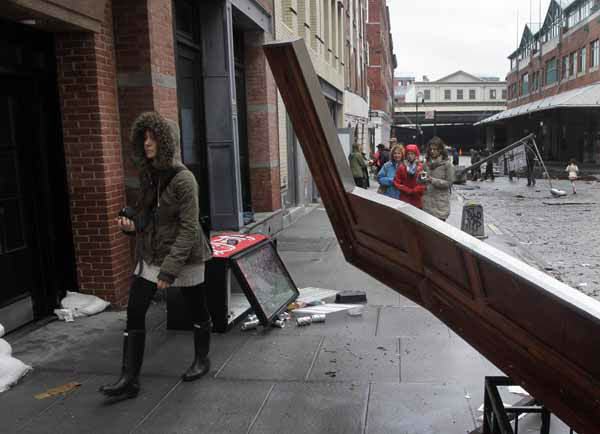 A woman walks around a downed building awning in New York&#39;s South Street Seaport, Tuesday, Oct. 30, 2012. New York City awakened Tuesday to a flooded subway system, shuttered financial markets and hundreds of thousands of people without power a day after a wall of seawater and high winds slammed into the city, destroying buildings and flooding tunnels. &#40;AP Photo&#47;Richard Drew&#41; <span class=meta>(AP Photo&#47; Richard Drew)</span>
