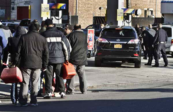 Police direct cars to pumps while people stand in line with containers for gas on Friday, Nov. 9, 2012 in the Brooklyn borough of New York. Police were at gas stations to enforce a new gasoline rationing plan that lets motorists fill up every other day. &#40;AP Photo&#47;Bebeto Matthews&#41; <span class=meta>(AP Photo&#47; Bebeto Matthews)</span>