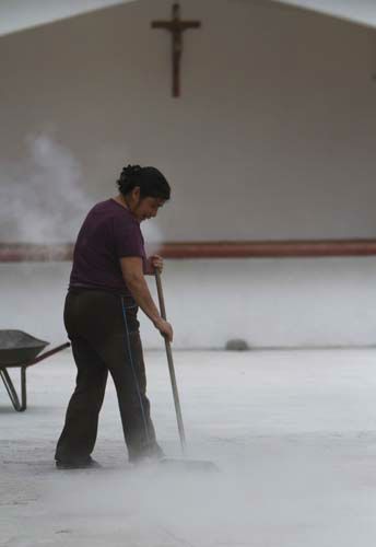 A resident sweeps volcano ash from the Popocatepetl volcano outside a church in San Pedro Nexapa, Mexico, Mexico, Monday, July 8, 2013. &#34;The ash affects us a lot, because we get our water from the snow melt from Popocatepetl, and right now we can&#39;t use the water for bathing, for cooking, we can&#39;t even give it to our animals,&#34; said Agustina Perez Gutierrez, a housewife in San Pedro Nexapa. &#34;The children get sore throats from the ash, and it affects the few vegetables and corn crops we are able to plant.&#34; &#40;AP Photo&#47;Marco Ugarte&#41; <span class=meta>(AP Photo&#47; Marco Ugarte)</span>