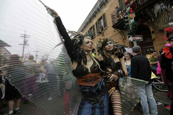 "<div class=""meta ""><span class=""caption-text "">Revelers show off their costumes as they march through the Bywater section of New Orleans during the Society of Saint Anne walking parade during Mardi Gras day, Tuesday, Feb. 12, 2013.  Despite threatening skies, the Mardi Gras party carried on as thousands of costumed revelers cheered glitzy floats with make-believe monarchs in an all-out bash before Lent.   Crowds were a little smaller than recent years, perhaps influenced by the forecast of rain. Still, parades went off as scheduled even as a fog settled over the riverfront and downtown areas.  (AP Photo/Gerald Herbert)</span></div>"