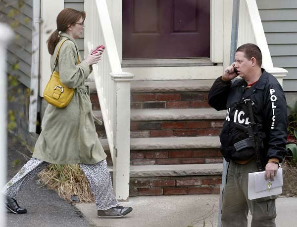 A woman heads away from a building in Cambridge, Mass., after being evacuated by police from her home next door, Friday, April 19, 2013.  Two suspects in the Boston Marathon bombing killed an MIT police officer, injured a transit officer in a firefight and threw explosive devices at police during a getaway attempt in a long night of violence that left one of them dead and another still at large Friday, authorities said as the manhunt intensified for a young man described as a dangerous terrorist. &#40;AP Photo&#47;Michael Dwyer&#41; <span class=meta>(AP Photo&#47; Michael Dwyer)</span>